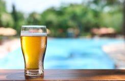 Κρύο γυαλί μπύρας στον πίνακα φραγμών στον υπαίθριο καφέ Στοκ Φωτογραφία