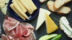 Κρύο ορεκτικό Κρύες περικοπές Πικάντικα τρόφιμα στο μαύρο υπόβαθρο, τοπ άποψη απόθεμα βίντεο