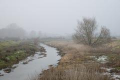 Κρύο misty χειμερινό τοπίο πέρα από το ρεύμα στην αγγλική επαρχία Στοκ εικόνες με δικαίωμα ελεύθερης χρήσης
