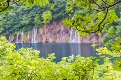 Κρύσταλλο - σαφής λίμνη βουνών με τους καταρράκτες που περιβάλλονται από το δάσος στο εθνικό πάρκο λιμνών Plitvice, Κροατία Στοκ Φωτογραφία