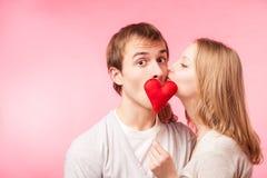 Κρύψιμο αγοριών φιλήματος κοριτσιών πίσω από τη λίγο κόκκινη καρδιά Στοκ Φωτογραφίες