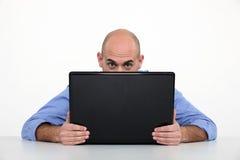 Κρύψιμο ατόμων πίσω από το lap-top στοκ εικόνα με δικαίωμα ελεύθερης χρήσης
