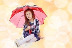 Κρύψιμο μικρών κοριτσιών κάτω από μια ομπρέλα Στοκ φωτογραφία με δικαίωμα ελεύθερης χρήσης