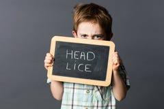 Κρύψιμο παιδιών Displeased πίσω από μια σχολική πλάκα που φοβίζει τις επικεφαλής ψείρες Στοκ Εικόνες
