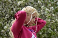 Κτένισμα της ουράς του μακριού νέου κοριτσιού ξανθών μαλλιών στο υπόβαθρο ενός ανθίζοντας δέντρου της Apple Στοκ φωτογραφία με δικαίωμα ελεύθερης χρήσης