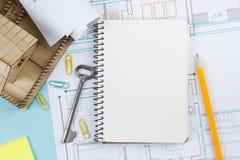 κτήμα έννοιας πραγματικό Κενό άσπρο σημειωματάριο στο αρχιτεκτονικό υπόβαθρο επιτραπέζιων σχεδιαγραμμάτων γραφείων με το κλειδί,  Στοκ εικόνα με δικαίωμα ελεύθερης χρήσης
