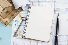 κτήμα έννοιας πραγματικό Κενό άσπρο σημειωματάριο στο αρχιτεκτονικό υπόβαθρο επιτραπέζιων σχεδιαγραμμάτων γραφείων με το κλειδί,  Στοκ Εικόνα