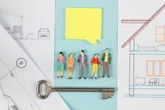 κτήμα έννοιας πραγματικό Κτήριο οικοδόμησης Η κενή ομιλία βράζει, αριθμοί παιχνιδιών ανθρώπων, πρότυπο σπίτι εγγράφου, σχεδιαγράμ Στοκ φωτογραφία με δικαίωμα ελεύθερης χρήσης