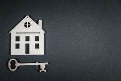 κτήμα έννοιας πραγματικό Μικρό ξύλινο σπίτι παιχνιδιών με τα κλειδιά στο γκρίζο υπόβαθρο στοκ φωτογραφίες με δικαίωμα ελεύθερης χρήσης