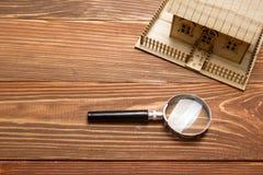 κτήμα έννοιας πραγματικό Πρότυπο σπίτι και ενίσχυση - γυαλί στον ξύλινο πίνακα Τοπ όψη Στοκ Φωτογραφίες
