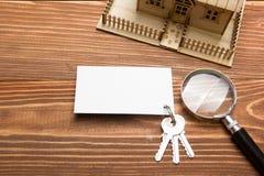 κτήμα έννοιας πραγματικό Πρότυπο σπίτι, κλειδιά, κενή επαγγελματική κάρτα, ενίσχυση - γυαλί στον ξύλινο πίνακα Τοπ όψη Στοκ Φωτογραφία