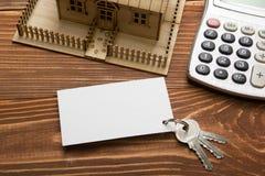 κτήμα έννοιας πραγματικό Πρότυπο σπίτι, κλειδιά, κενή επαγγελματική κάρτα, μάνδρα και υπολογιστής στον ξύλινο πίνακα Τοπ όψη Στοκ Εικόνες