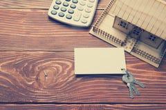 κτήμα έννοιας πραγματικό Πρότυπο σπίτι, κλειδιά, κενοί επαγγελματική κάρτα και υπολογιστής στον ξύλινο πίνακα Τοπ όψη εικόνα που  Στοκ φωτογραφία με δικαίωμα ελεύθερης χρήσης