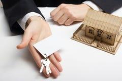 κτήμα έννοιας πραγματικό Χέρια που κρατούν την κενή επαγγελματική κάρτα με τα κλειδιά Στοκ φωτογραφία με δικαίωμα ελεύθερης χρήσης
