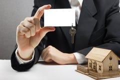κτήμα έννοιας πραγματικό Χέρια που κρατούν την κενή επαγγελματική κάρτα με τα κλειδιά Στοκ Εικόνα