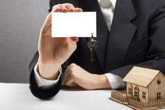κτήμα έννοιας πραγματικό Χέρια πρακτόρων που κρατούν την κενή επαγγελματική κάρτα με τα κλειδιά Στοκ Φωτογραφίες