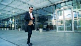 Κτήριο επιχειρησιακών συστάδων και ένα άτομο που περπατά κοντά να ενεργοποιήσει ένα τηλέφωνο απόθεμα βίντεο