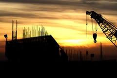 Κτήριο οικοδόμησης γερανών σκιαγραφιών στο ηλιοβασίλεμα Στοκ φωτογραφία με δικαίωμα ελεύθερης χρήσης