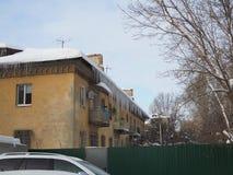 Κτήριο που καλύπτεται με τα μεγάλα παγάκια Τα παγάκια κρεμούν από τη στέγη, κάθετη ένωση σταλακτιτών πάγου από τη στέγη στοκ εικόνες