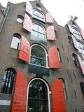 Κτήριο τούβλου με τα κόκκινα παραθυρόφυλλα Στοκ Φωτογραφία