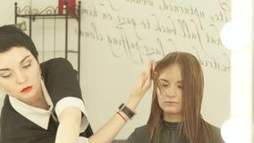 Κτενίζοντας και ψεκάζοντας νερό θηλυκών κομμωτών στην τρίχα σκελών πρίν κόβει στο σαλόνι ομορφιάς Κλείστε haircutter να αποτελέσε φιλμ μικρού μήκους