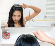 κτενίζοντας το τρίχωμα κοριτσιών αυτή Στοκ εικόνα με δικαίωμα ελεύθερης χρήσης