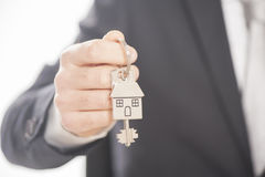 Κτηματομεσίτης που δίνει τα κλειδιά σπιτιών σε ένα ασημένιο σπίτι που διαμορφώνεται keychain Στοκ Εικόνες