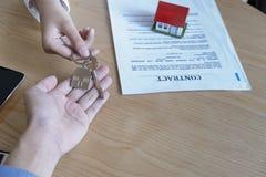 Κτηματομεσίτης που δίνει τα κλειδιά σπιτιών στη συμφωνία ιδιοκτητών και σημαδιών στην αρχή στοκ εικόνα
