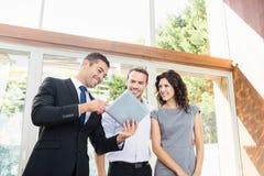 Κτηματομεσίτης που παρουσιάζει στο ζεύγος νέο σπίτι στοκ εικόνες με δικαίωμα ελεύθερης χρήσης
