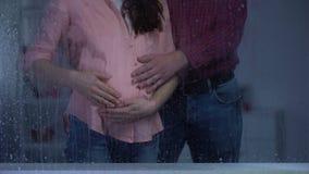 Κτυπώντας έγκυος γυναίκα ζεύγους tummy πίσω από το βροχερό παράθυρο, προσδοκία μωρών απόθεμα βίντεο