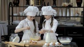 Κτυπώντας αυγά νέων κοριτσιών στο κύπελλο γυαλιού στον ξύλινο πίνακα φιλμ μικρού μήκους