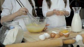 Κτυπώντας αυγά νέων κοριτσιών στο κύπελλο γυαλιού στον ξύλινο πίνακα απόθεμα βίντεο