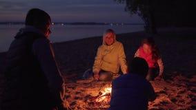 Κτυπώντας γιος πατέρων στο κεφάλι από την πυρά προσκόπων κατά τη διάρκεια του οικογενειακού πεζοπορώ στην παραλία απόθεμα βίντεο
