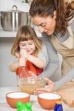 Κτύπημα γυναικών και παιδιών χαμόγελου για να κάνει ένα κέικ Στοκ εικόνες με δικαίωμα ελεύθερης χρήσης