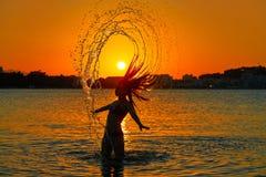Κτύπημα τρίχας κτυπήματος κοριτσιών στην παραλία ηλιοβασιλέματος στοκ φωτογραφίες