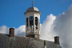 Κτύπος και ρολόι αιθουσών πόλεων ενάντια στο μπλε ουρανό, σκοτεινή προσέγγιση σύννεφων Στοκ Εικόνες