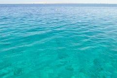 Κυανή ακτή με την άσπρη άμμο, καθαρό και σαφές μπλε νερό μια ηλιόλουστη ημέρα Στοκ εικόνα με δικαίωμα ελεύθερης χρήσης