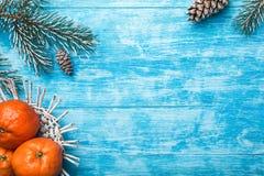 Κυανό ξύλινο υπόβαθρο πράσινο δέντρο έλατου Φρούτα με το μανταρίνι Ευχετήρια κάρτα Χριστουγέννων και νέο έτος στοκ εικόνες