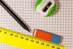 Κυβερνήτης, μολύβι, sharpener και γόμα στο φύλλο σημειωματάριων στοκ εικόνες