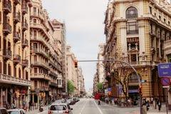Κυκλοφορία σε μια οδό της Βαρκελώνης με τα όμορφα κτήρια κατά μήκος της άκρης του δρόμου στοκ φωτογραφίες