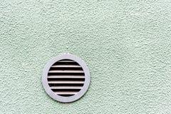 Κυκλικός πλαστικός εξαεριστήρας στα άσπρα πράσινα κάγκελα εξαερισμού τοίχων Στοκ φωτογραφία με δικαίωμα ελεύθερης χρήσης