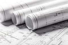 Κυλημένα σχεδιαγράμματα σπιτιών και σχέδια κατασκευής στοκ εικόνες