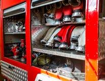 Κυλημένες μάνικες πυρκαγιάς, που τακτοποιούνται στις σειρές, στο διαμέρισμα γαντιών του πυροσβεστικού οχήματος στοκ εικόνες