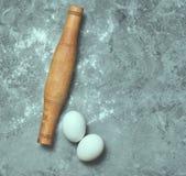 Κυλώντας καρφίτσα, αλεύρι, αυγά σε έναν συγκεκριμένο πίνακα μαγειρεύοντας καθορισμένα εργαλεία κουζινών Στοκ Εικόνες