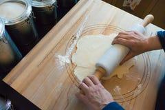 Κυλώντας κρούστα πιτών γυναικών σε έναν ξύλινο πίνακα Στοκ Εικόνες