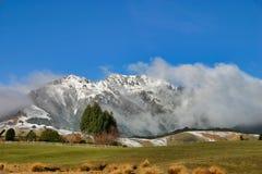 Κυλώντας τομείς με τα χιονισμένα βουνά στοκ εικόνες με δικαίωμα ελεύθερης χρήσης