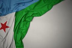 Κυματίζοντας εθνική σημαία του Τζιμπουτί σε ένα γκρίζο υπόβαθρο στοκ φωτογραφίες με δικαίωμα ελεύθερης χρήσης