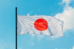 Κυματίζοντας ζωηρόχρωμη σημαία της Ιαπωνίας στο μπλε ουρανό Στοκ Φωτογραφίες