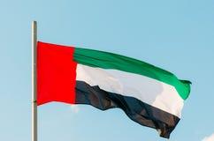 Κυματίζοντας ζωηρόχρωμη σημαία των Ηνωμένων Αραβικών Εμιράτων στο μπλε ουρανό Στοκ Φωτογραφίες