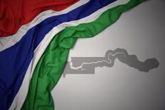 Κυματίζοντας ζωηρόχρωμοι εθνική σημαία και χάρτης της Γκάμπιας απεικόνιση αποθεμάτων